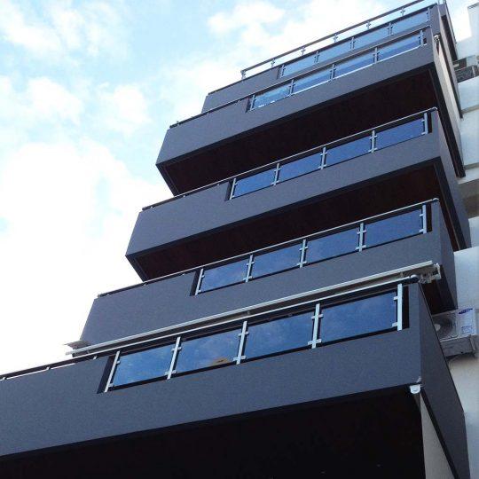 Κατασκευή πολυκατοικίας με μπαλκόνια διακοσμημένα με κάγκελα αλουμινίου και γυαλιού