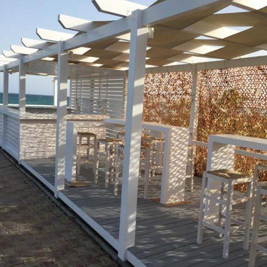Ξύλινη κατασκευή beach bar με δίχτυ σκίασης και πλεκτή πέργκολα και ειδικό φωτισμό